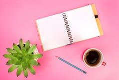 秀丽博克概念照片 绿色植物、笔记本、笔和咖啡在桃红色背景的 免版税库存图片