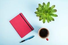 秀丽博克概念照片 绿色植物、笔记本、笔和咖啡在桃红色背景的 图库摄影