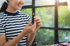 秀丽博客作者礼物秀丽化妆用品,当坐在记录的录影的时前面照相机 美丽的妇女用途唇膏 库存图片