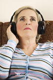 秀丽听音乐前辈妇女 免版税库存图片