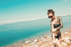 秀丽和健康 室外温泉 抹上在身体,海滩死海的妇女泥面具 休闲旅游业,健康生活方式,身体汽车 免版税库存照片