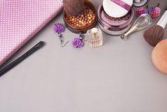 秀丽和化妆用品概念 香水瓶、cosmetcis、粉末和刷子 桃红色背景 复制空间 顶视图 免版税库存图片