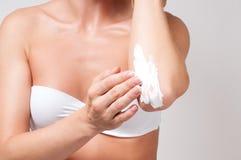 秀丽和机体关心 应用在她的手肘的妇女奶油 图库摄影
