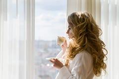 秀丽咖啡饮用的女孩 美丽的妇女开幕,看窗口和享用她的早晨咖啡 库存照片