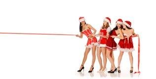 秀丽四女孩拉红色丝带 免版税库存图片