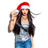 秀丽圣诞节有长的头发的时装模特儿女孩在红色圣诞老人帽子 免版税库存照片