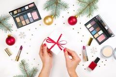 秀丽在白色背景组成化妆用品设置与圣诞节装饰和提出在妇女` s手平的位置 图库摄影