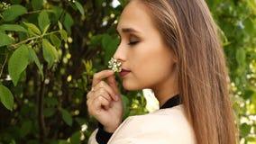 秀丽女孩嗅到的花 特写镜头 概念自然有机健康,化妆用品产品 室外 股票视频
