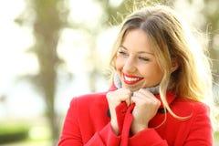 秀丽女孩在冬天温暖地给佩带的红色夹克穿衣 免版税库存照片