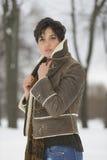 秀丽女孩在冷淡的冬天公园 户外 飞行雪花 图库摄影