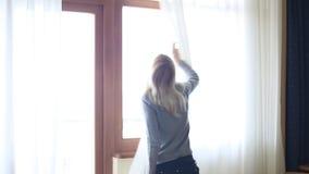 秀丽女孩在屋子里打开在大窗口的帷幕并且让光 查找视窗 影视素材