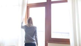 秀丽女孩在屋子里打开在大窗口的帷幕并且让光 查找视窗 股票视频