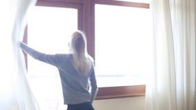 秀丽女孩在屋子里打开在大窗口的帷幕并且让光 查找视窗 股票录像