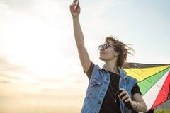 秀丽女孩在运行与在日落天空的风筝的吉恩夹克 查出的黑色概念自由 库存照片