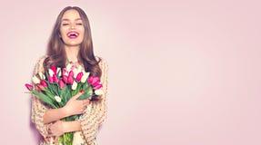 秀丽女孩藏品春天郁金香 接受五颜六色的郁金香的花束愉快的美女 库存照片