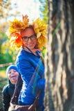 秀丽妇女和她的儿子秋天停放 免版税库存照片