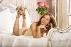 秀丽妇女在白色内部的床上 免版税库存图片