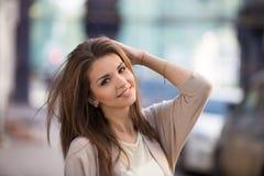 秀丽妇女室外画象有完善的微笑的走在街道上的 免版税库存图片