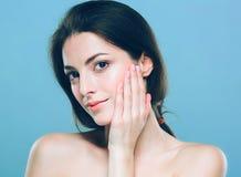 秀丽妇女面孔画象 有完善的新鲜的干净的皮肤的美丽的温泉模型女孩 蓝色背景灰色 免版税库存照片