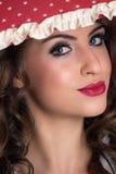 年轻秀丽妇女画象在有看照相机的红色唇膏的伞下 图库摄影