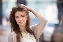 秀丽妇女画象有完善的微笑的走在街道上和看照相机的 免版税库存图片
