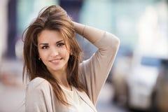 秀丽妇女画象有完善的微笑的走在街道上和看照相机的 库存照片