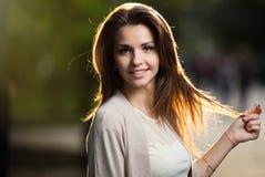 秀丽妇女画象有完善的微笑的走在街道上和看照相机,日落光的 库存图片