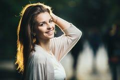 秀丽妇女画象有完善的微笑的走在街道上和看照相机,日落光的 免版税库存照片