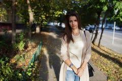 秀丽妇女画象有完善的微笑的走在街道上和看照相机,日落光的 库存照片