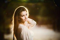 秀丽妇女画象有完善的微笑的走在街道上和看照相机,日落光的 免版税库存图片