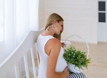 秀丽孕妇坐一条白色长凳 产科概念 免版税图库摄影
