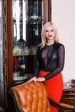 秀丽富有的内部的,佩带的黑礼服时髦的典雅的白肤金发的妇女 库存图片