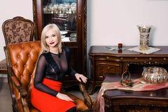 秀丽富有的内部的,佩带的黑礼服时髦的典雅的白肤金发的妇女 免版税库存照片