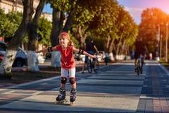 秀丽小女孩四轮溜冰在城市公园在温暖的阳光照耀夏日 库存图片