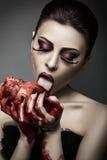 秀丽少妇舔从人的心脏的血液 免版税库存照片