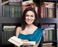 秀丽少妇阅读书画象在图书馆里 免版税图库摄影