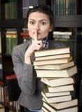 秀丽少妇阅读书画象在图书馆里 免版税库存照片