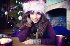秀丽庆祝圣诞节的魅力妇女佩带礼服、欢乐圣诞节背景与圣诞树的火和露指手套 免版税库存照片