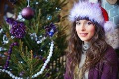 秀丽庆祝圣诞节的魅力妇女,戴着狂欢节帽子 免版税库存照片