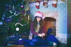 秀丽庆祝圣诞节的魅力妇女,戴着狂欢节帽子 库存照片