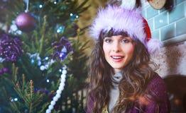 秀丽庆祝圣诞节的魅力妇女,戴着狂欢节帽子 免版税图库摄影