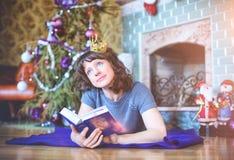秀丽庆祝圣诞节的魅力妇女,读书wearin 免版税库存照片