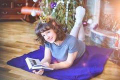 秀丽庆祝圣诞节的魅力妇女,读书wearin 免版税库存图片