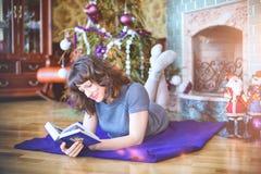 秀丽庆祝圣诞节的魅力妇女,读书wearin 免版税图库摄影