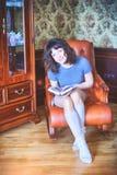 秀丽庆祝圣诞节的魅力妇女,读佩带礼服和冠的书,与圣诞节的欢乐圣诞节背景 库存图片