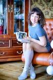 秀丽庆祝圣诞节的魅力妇女,读佩带礼服和冠的书,与圣诞节的欢乐圣诞节背景 免版税图库摄影