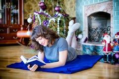 秀丽庆祝圣诞节的魅力妇女,读穿礼服的书,与圣诞树fi的欢乐圣诞节背景 免版税库存图片