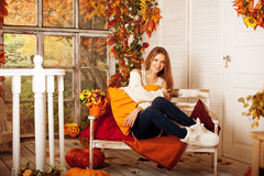 秀丽微笑在黄色和橙色澳大利亚门廊的秋天妇女  免版税图库摄影