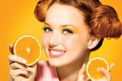 秀丽快乐的青少年的女孩用水多的桔子 库存图片