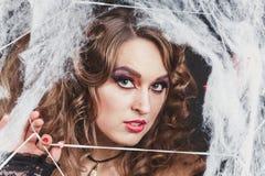 秀丽性感的巫婆女孩画象在蜘蛛网捉住了 时尚艺术设计 美丽的哥特式式样女孩与 免版税库存照片